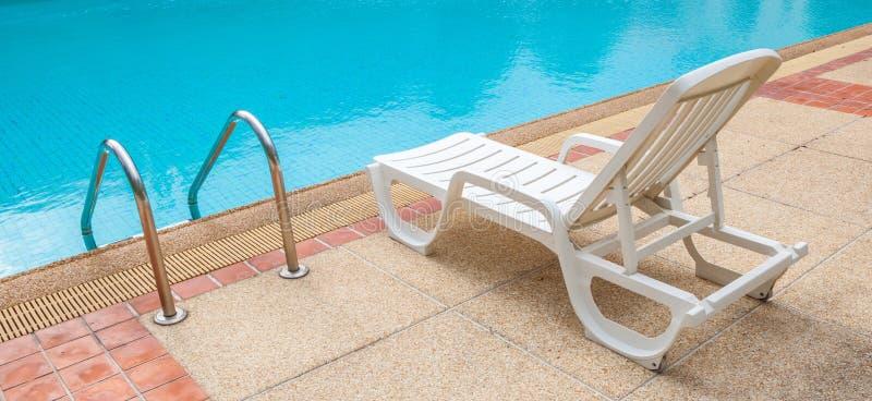 白色躺椅在梯子附近的水池边;蓝色游泳的p 免版税库存图片