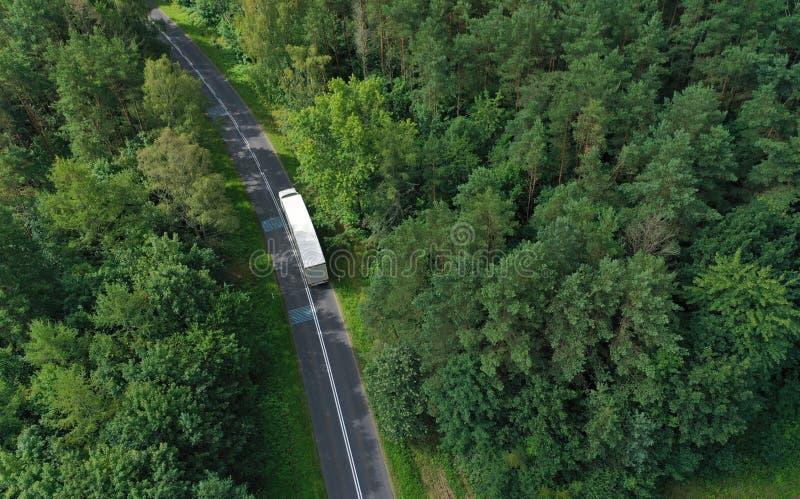 白色载货车在弯曲沥青路上穿林的无人机透视 免版税图库摄影