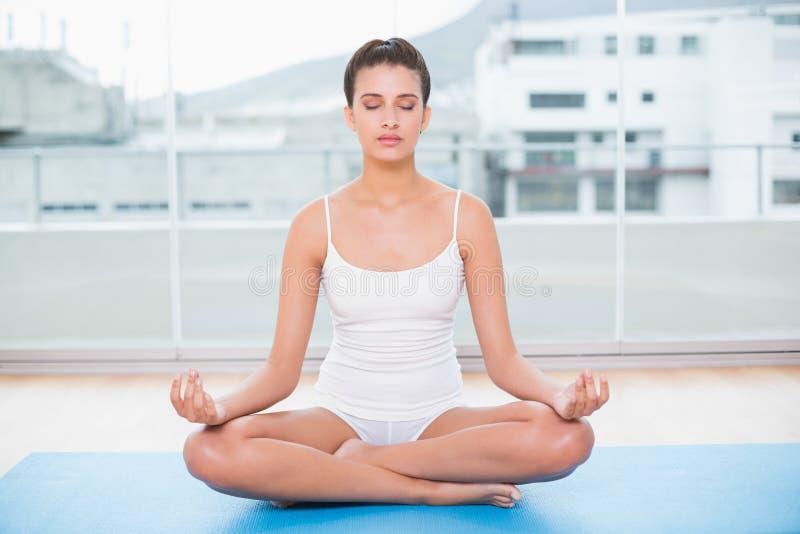 白色运动服实践的瑜伽的平安的自然棕色毛发的妇女 免版税库存图片