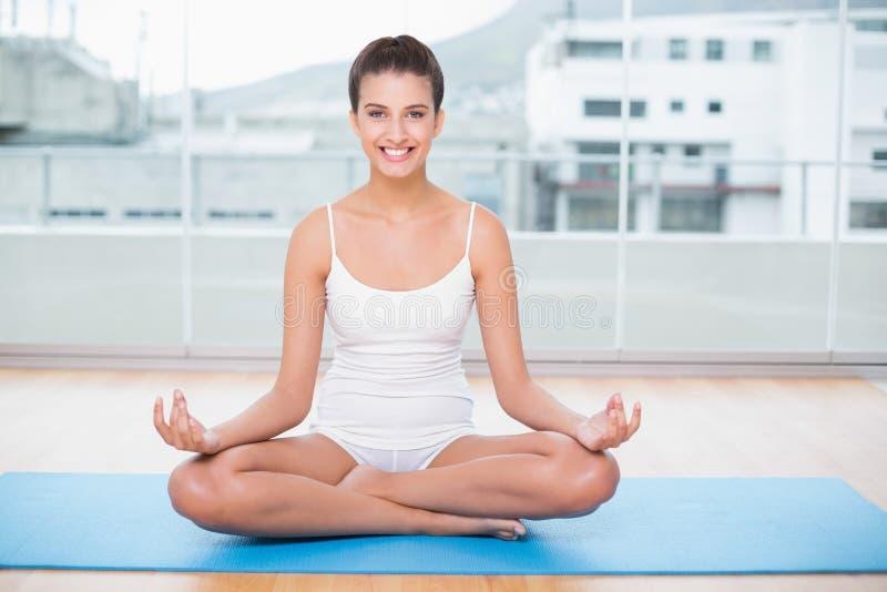 白色运动服实践的瑜伽的微笑的自然棕色毛发的妇女 图库摄影