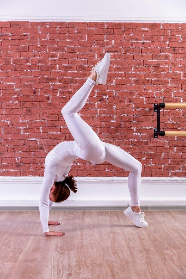 白色连衫裤的年轻美丽的灵活的女孩在舞蹈演播室摆在 舒展和身体芭蕾题材 现代舞趋向 库存图片
