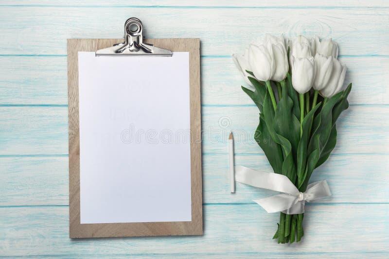 白色郁金香花束与片剂的在蓝色木板 库存照片