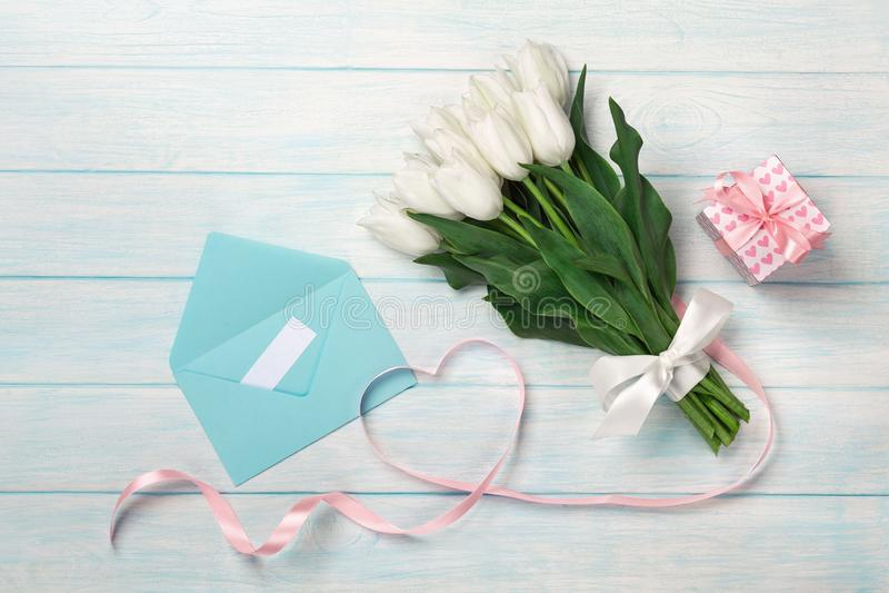白色郁金香花束和以心脏的形式一条桃红色丝带与一个礼物盒、爱笔记和颜色信封在蓝色木 免版税库存照片