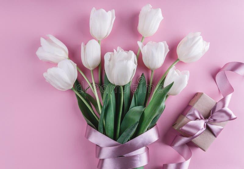 白色郁金香花花束与礼物的在桃红色背景 贺卡或婚礼邀请 图库摄影