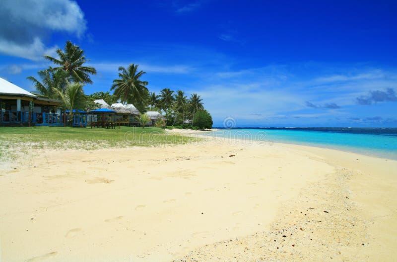 白色金黄沙子和珊瑚蓝色海水与玻利尼西亚海滩前的房子使fales,Manase,萨摩亚,萨瓦伊靠岸 免版税图库摄影