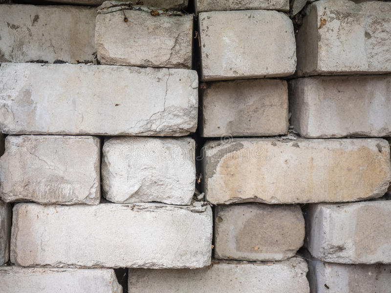 白色钙硅酸盐砖被堆在彼此顶部 被修造的老,破裂和切削的砖,粗砺的堆