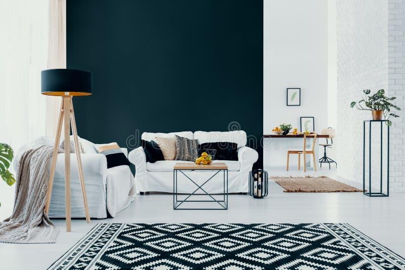 白色长沙发对在现代客厅内部的黑墙壁与被仿造的地毯 实际照片 免版税库存图片