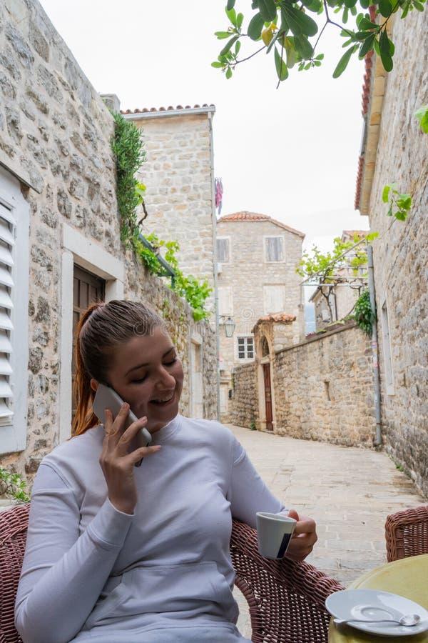 白色长的衬衣饮用的咖啡的少女在大阳台和打在她的智能手机的一次电话 拿着在a的妇女一个杯子 免版税库存图片
