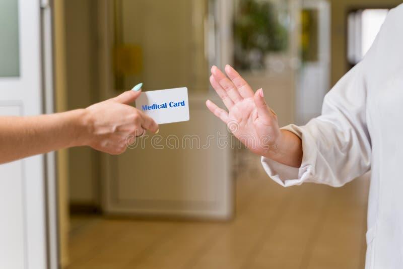 白色长袍的拒绝中年女性的医生医疗卡片 库存图片