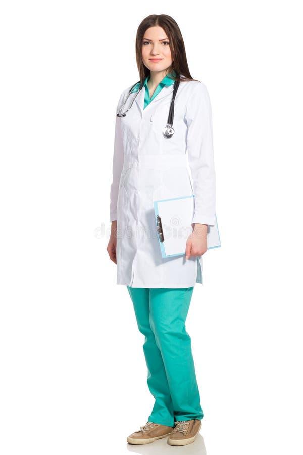 白色长袍的年轻女性医生有剪贴板和听诊器的 免版税库存图片