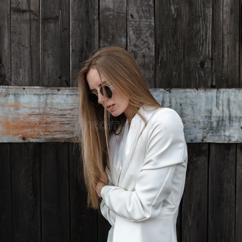 白色长裤的性感的女孩关于木墙壁 库存照片