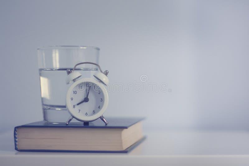 白色闹钟和杯在蓝色口气的水 库存图片