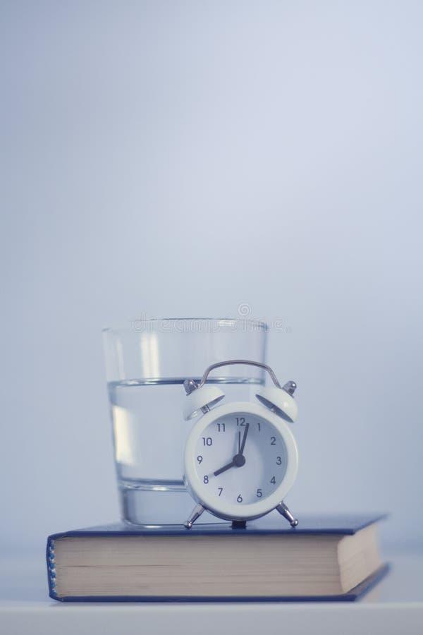 白色闹钟和杯在蓝色口气的水 库存照片