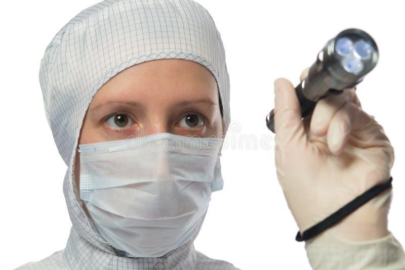 白色防护套服的妇女,在她的手上学习和拿着一个手电 免版税库存图片