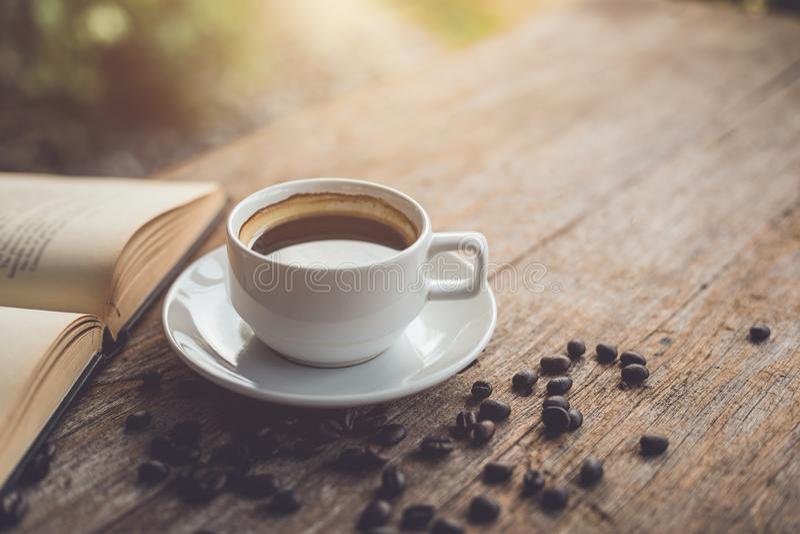 白色陶瓷咖啡杯在木桌上的黑热的americano 免版税库存照片