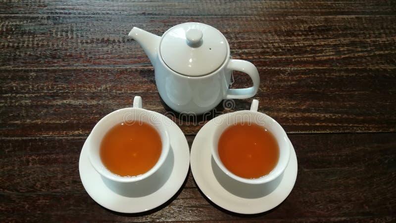 白色陶瓷茶和在棕色木桌背景的茶罐 免版税库存照片