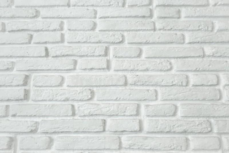 白色难看的东西砖墙纹理背景,砖墙绘与白色油漆 免版税库存照片