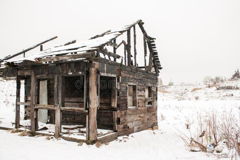 白色雪的被烧的木房子 库存照片