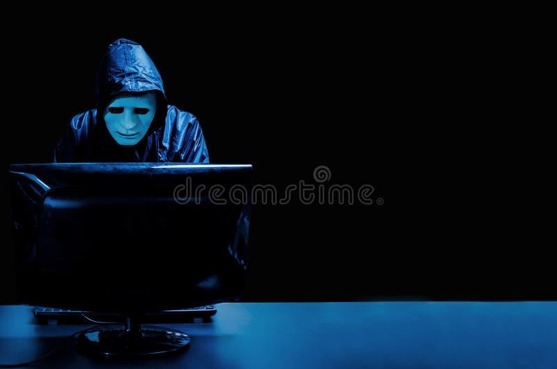 白色面具和有冠乌鸦的匿名计算机黑客 被遮暗的黑暗的面孔身分在中部和乱砍它与他的计算机, 库存图片