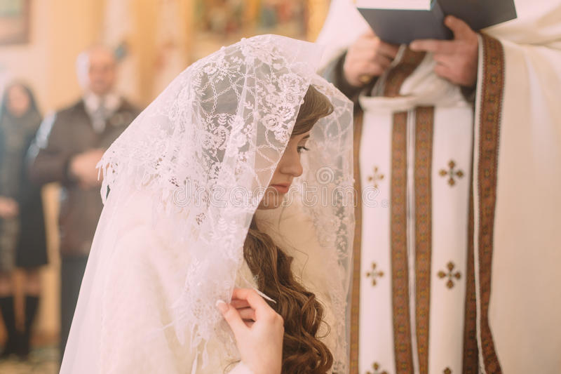 白色面纱的新娘在婚礼期间的教会 图库摄影