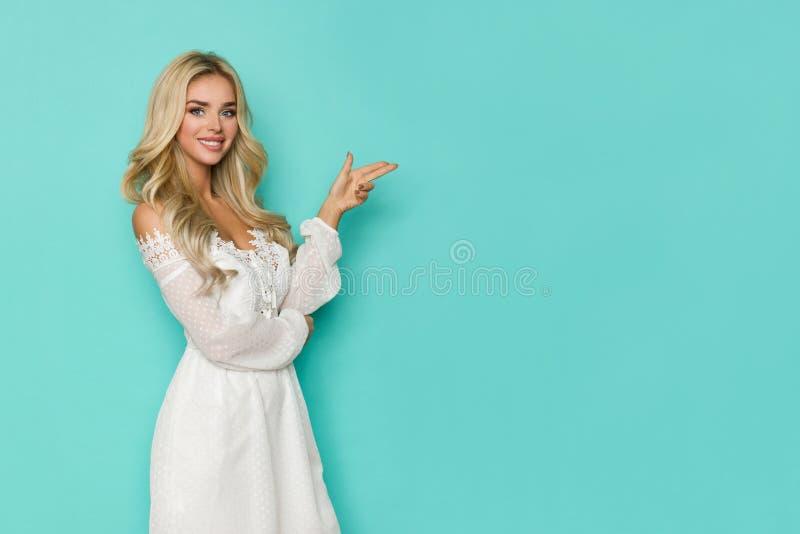 白色鞋带礼服的美丽的白肤金发的妇女指向并且微笑着 免版税库存照片