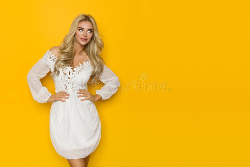 白色鞋带礼服的美丽的白肤金发的妇女注视着对边黄色拷贝空间 库存照片
