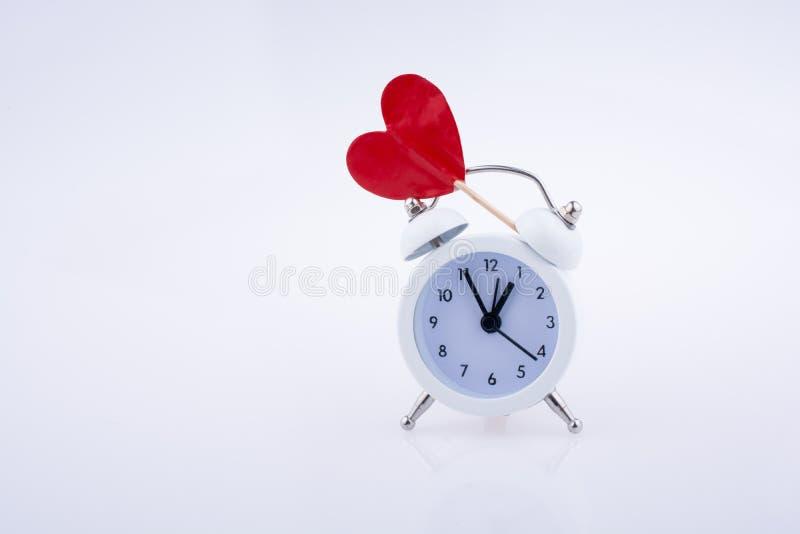 白色颜色闹钟和红色心脏形状 库存照片