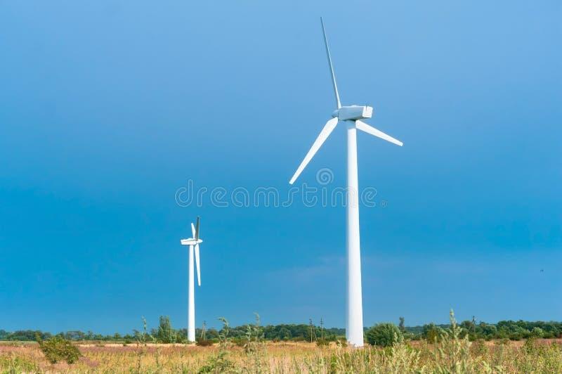 白色风力植物,在领域的两台风轮机 库存图片
