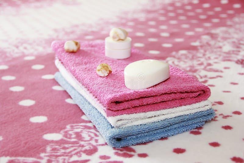 白色香皂和装饰以桃红色特里毛巾为背景 免版税库存照片
