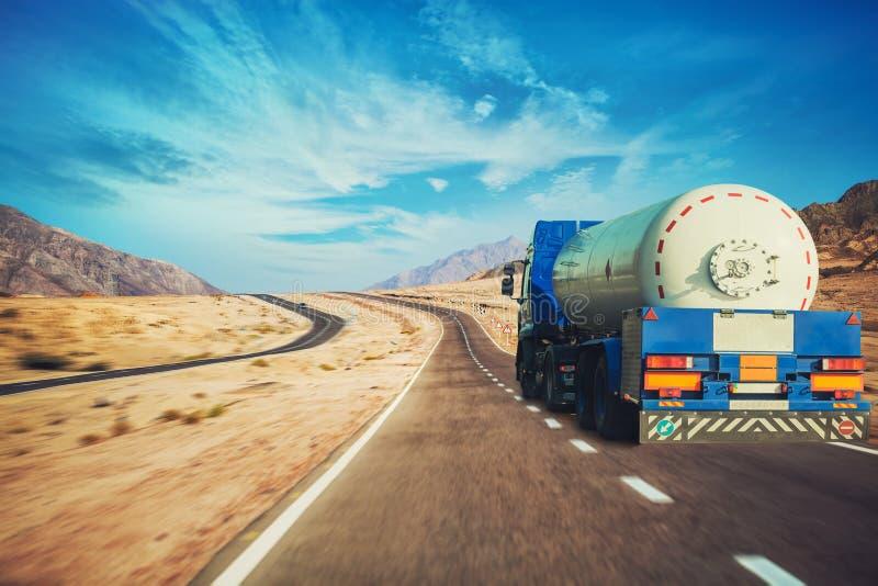 白色驾驶沿美丽如画的沙漠山高速公路的罐车和卡车 免版税库存照片