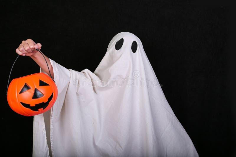 白色鬼魂用在黑背景的一个南瓜 万圣节节日晚会 库存照片