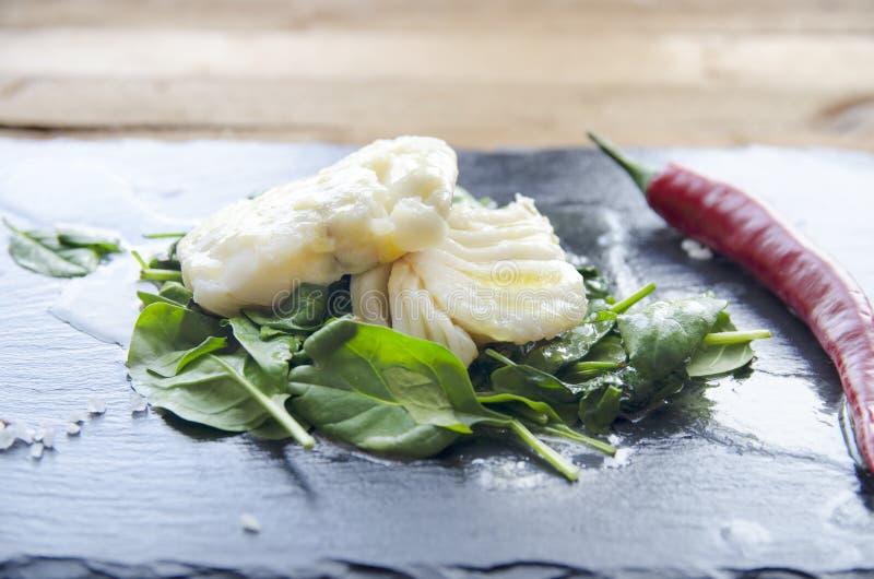 白色鱼内圆角用在油煎的菠菜的辣椒 灰色背景 免版税图库摄影