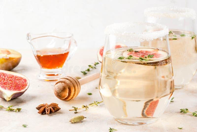 白色鸡尾酒用无花果、李子、蜂蜜和麝香草 库存图片
