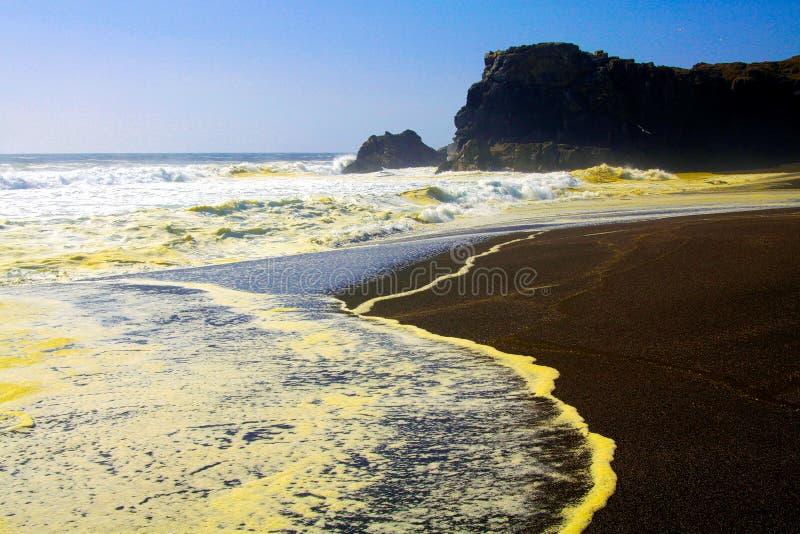 白色黄色起泡沫的水海浪与黑熔岩沙滩和被弄脏的天际形成对比 免版税库存照片