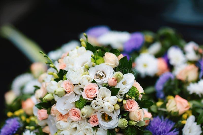 白色,桃红色和紫外花美丽的婚礼花束与金子婚戒,文本的地方的 免版税库存图片