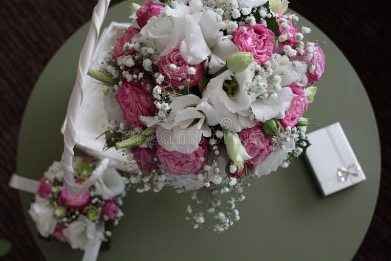 白色,桃红色和绿色花新娘花束在一个白色篮子 免版税库存图片