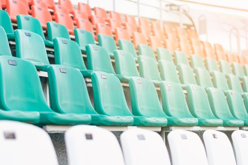 白色,红色和薄菏色塑料位子,安排在行在体育场内 免版税库存图片