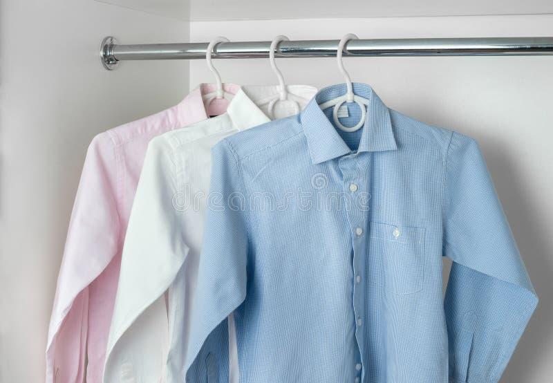 白色,蓝色和桃红色清洗垂悬在挂衣架的被电烙的人的衬衣 免版税库存图片