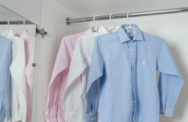 白色,蓝色和桃红色清洗被电烙的人的衬衣 免版税库存图片