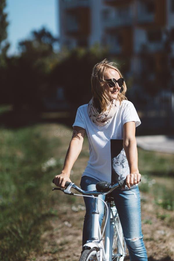 白色,被恢复的,减速火箭的自行车的妇女 库存图片