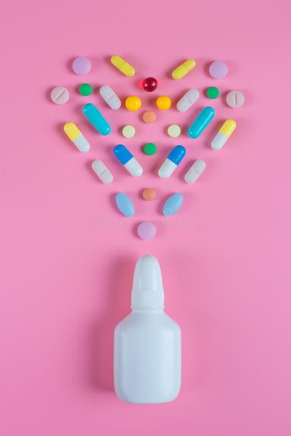 白色,黄色,红色,蓝色药片、片剂和白色瓶在桃红色背景 免版税库存照片