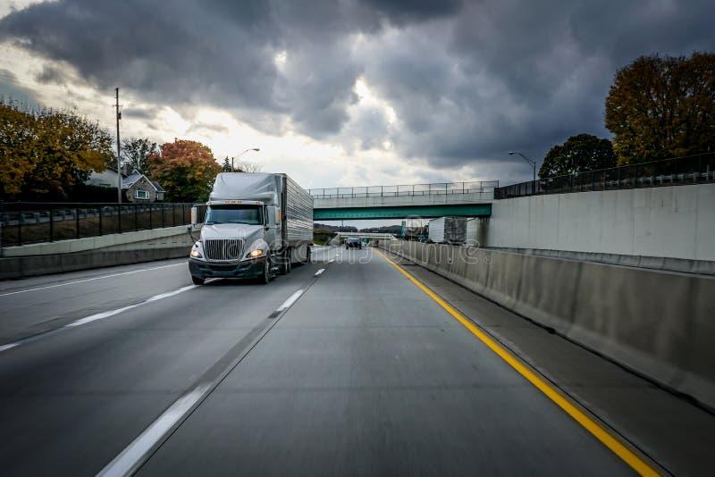 白色18在高速公路的轮车半卡车有在天空的暴风云的 库存图片