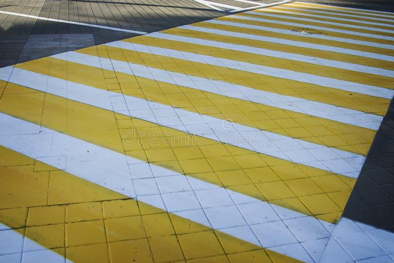 白色黄色行人穿越道斑马线 与阴影的行人交叉路 图库摄影