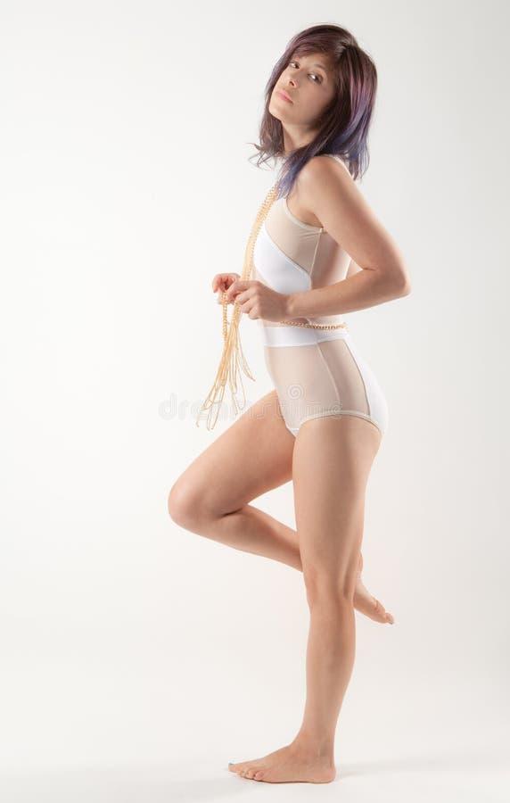 白色紧身衣裤和十字架身体链子的妇女 免版税库存照片