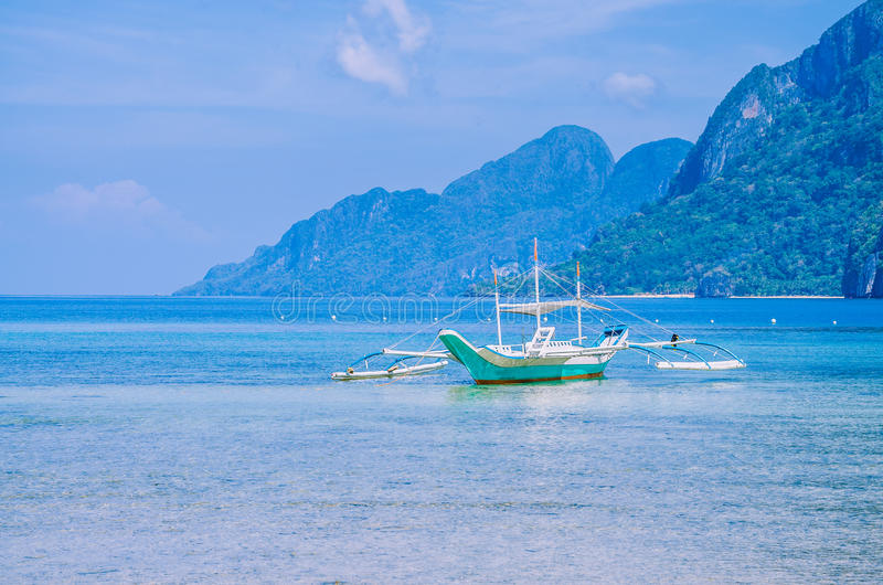 白色banca小船在镇静蓝色海洋,七个特攻队在背景, El Nido,菲律宾中靠岸 库存照片