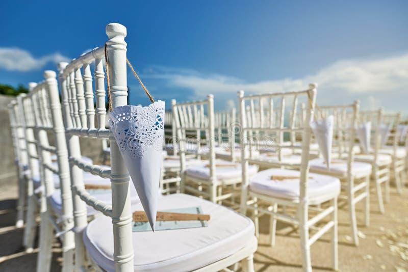 白色chiavari为有锥体的海滩婚礼地点主持玫瑰花瓣垂悬的特写镜头 图库摄影