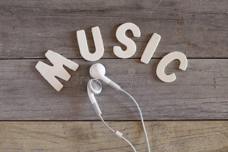 白色earbuds和词'音乐'在木桌上 免版税库存图片