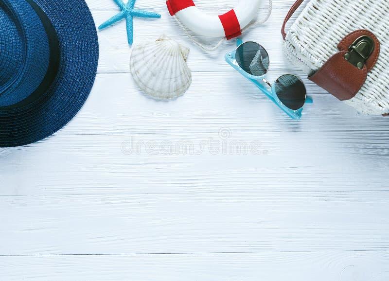 白色eco藤条袋子、海星壳太阳镜和妇女的蓝色帽子在白色木桌上 夏天背景,假期,旅行 免版税库存照片