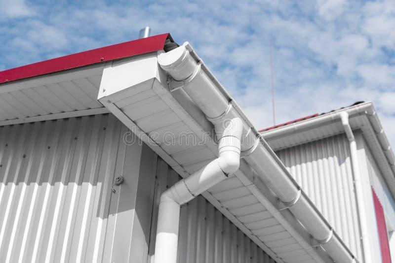 白色guttering在有红色屋顶的一个家反对蓝天 塑料guttering的系统 Guttering排水设备管子外部 免版税图库摄影
