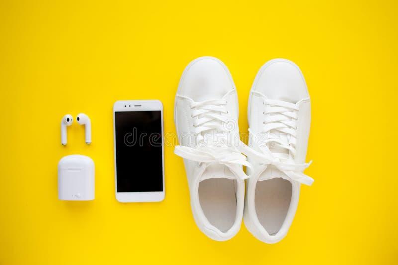 白色sneackers、无线耳机和智能手机在明亮的黄色背景说谎 免版税库存照片